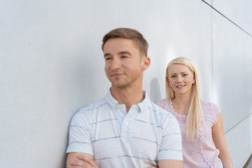 Young man and woman leaning on a white wall