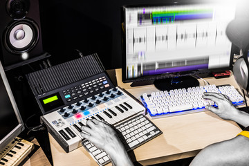 male producer hands composing music on midi keyboard, studio equipment and computer in studio