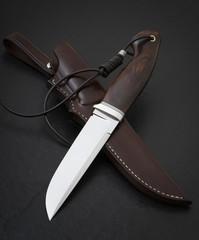 Hunting knife handmade on a black background. Leather Sheath Handmade