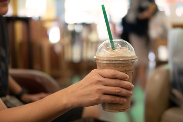Woman holding plastic glass of iced coffee with milk