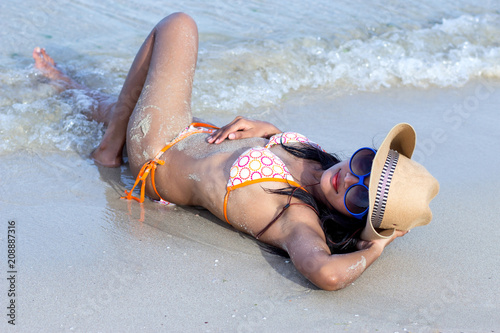 c7eb668a85c57 Attractive woman with cowboy hat lying on the sea beach