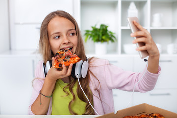 Young teenager girl eating pizza in the kitchen - making a selfie