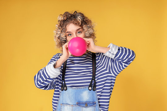 Cute young woman inflating balloon on color background