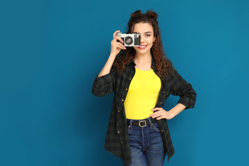 Portrait of beautiful young woman with camera on color background