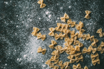 elevated view of farfalle pasta on table covered by flour