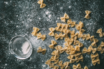 elevated view of farfalle pasta and sieve on table covered by flour