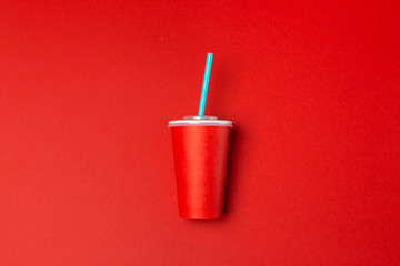 Red paper cup isolated on red.