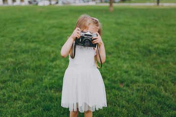 Portrait of little cute child baby girl in light dress holding retro vintage photo camera on green grass in park. Mother, little kid daughter. Mother's Day, love family, parenthood, childhood concept.