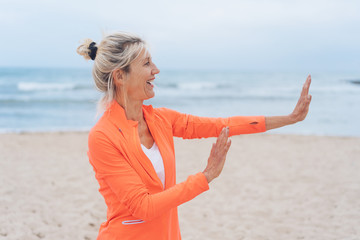 Mature woman giving a halt sign on a beach