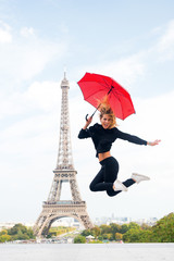 Lady with umbrella excited about visiting Eiffel Tower, sky background. Lady tourist sporty and active in Paris city center jumps up. Girl tourist enjoy walk and sightseeing. Dreams come true concept
