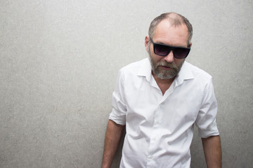 A man in a shirt with a beard in glasses is standing by the wall