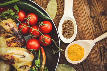 fried chicken wings in a frying pan. tomatoes and spices. wooden background