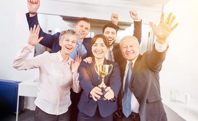 Start-Up Business Team als Gewinner hält Pokal