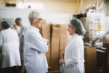 Two young joyful female workers in sterile cloths are having a chat while standing in factory cargo room.
