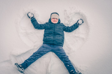 Boy in the snow makes a snow angel, winter snow frosty weather