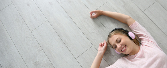 Blond girl relaxing on wooden flooring with headphones on, template