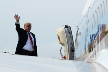 U.S. President Donald Trump waves as he boards Air Force One after his summit with North Korean leader Kim Jong Un in Singapore