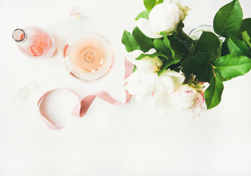 Flat-lay of rose wine in glass and bottle, pink decorative ribbon and bouquet of peony flowers over white table background, top view, copy space. Summer celebration or wedding greeting card or