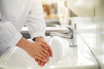 Female worker is sterilizing hands before work.