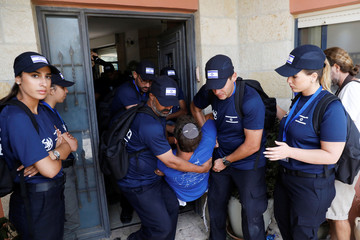 Israeli security forces carry a man out of a house during the evacuation of Jewish settler families from the illegal outpost of Netiv Ha'avot in the occupied West Bank