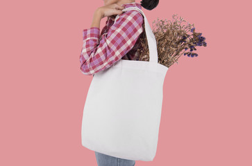 Girl is holding bag canvas fabric with flower for mockup blank template isolated on pink background.