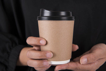 Hand holding coffee paper cup. mock up for creative design branding.