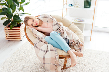 Portrait of sleepy lovely girl sleeping in cane armchair with barefoot in comfortable apartment flat covered by plaid having sweet dreams relaxing after hard day
