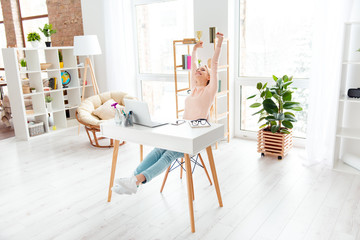 Portrait of cheerful positive girl sitting in white room at desktop making stretching with raised arms while preparing for exams enjoying timeout dreaming about weekend holiday