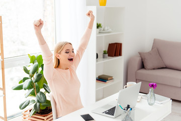 Portrait of successful positive girl celebrating pass exams with raised fists looking at screen of computer having great results sitting in modern white room indoor
