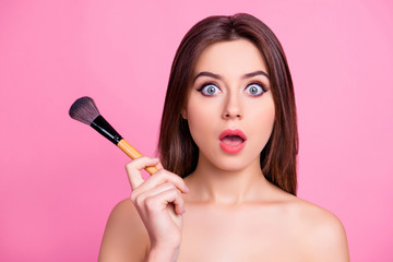 Close up portrait of shocked beautiful attractive pop-eyed pretty surprised scared make up artist holding a brush for blusher and powder in a hand, isolated on pink background