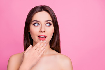 Wow! Portrait of wondered impressed beautiful attractive cute lovely woman is touching her chin looking up on empty blank copy space, isolated on pink background
