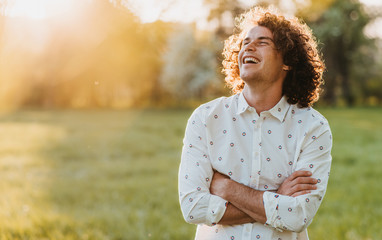 Handsome happy young male smiling with curly hair posing in the city park looking at the sky, cross his hands and dreaming. Copy space for your advertising. People, lifestyle and emotion concept Wall mural