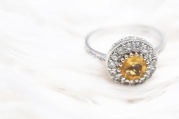 Yellow gem stone and diamond ring on white fabric