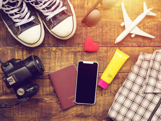 flat lay of passport ,mobile, plane model , sneakers , wallet , camera and traveler's accessories items on wooden background with copy space. travel and vacation concept