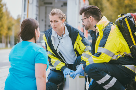 Emergency medics talking to injured woman in front of ambulance
