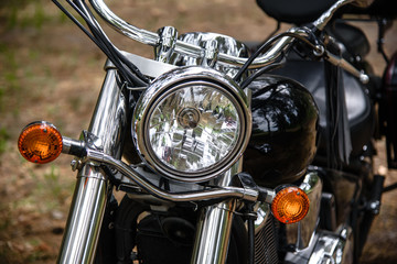 The headlight of a motorcycle close-up, in front of a bike