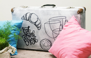 Suitcase with an inscription. Phrase Eat, Drink, Enjoy. Brush Pen lettering with pillow and plants like a cozy decoration
