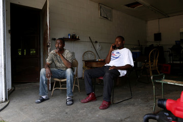 Kelvin Bradfield, left, who worked on Mike Espy's first campaign, sits with his friend Nicholas Lov as they take a break from washing cars in Yazoo City