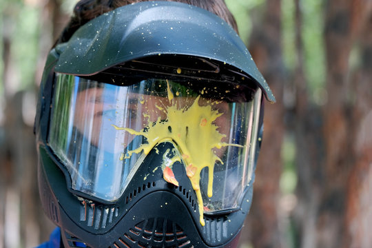 Yellow blot paint on a protective glass mask for playing paintball outside. The head of a young man in a helmet.