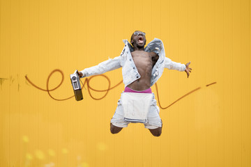 African man jumping with vintage radio device.