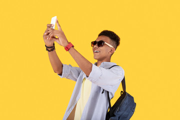 For my blog. Positive excited man holding a smartphone while taking a video for his blog
