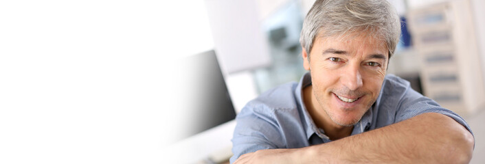 Smiling mature man relaxing in office chair, template