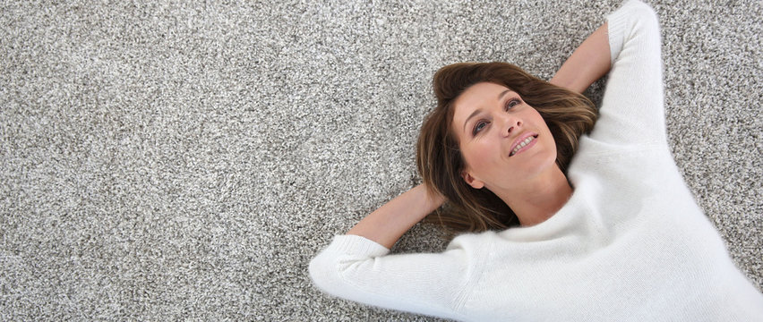 Upper view of woman relaxing on carpet at home, template