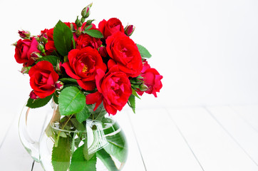 Home roses in a glass vase on a white wooden table. With copy space