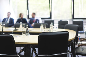 Bottles of water and glasses on the empty meeting table and people in the background. Business concept