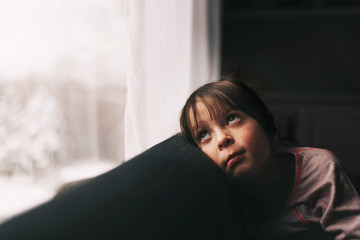 Girl sitting on a couch looking through a window