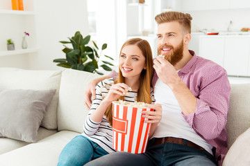 Entertainment comfort cozy happiness leisure lifestyle snack feelings emotions concept. Cute lovely couple watching cartoons on tv in house sitting on divan holding basket of pop-corn living room