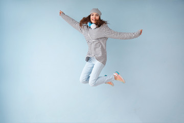 Jumping young woman with headphones on color background