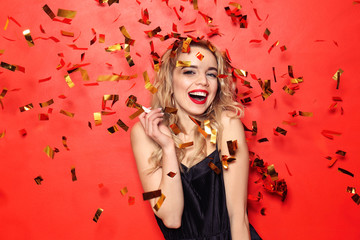 Portrait of beautiful young woman with party whistle and falling confetti on color background