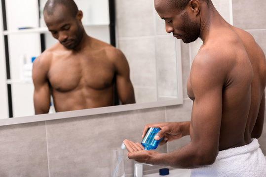 handsome young man pouring after shave lotion onto hand at bathroom